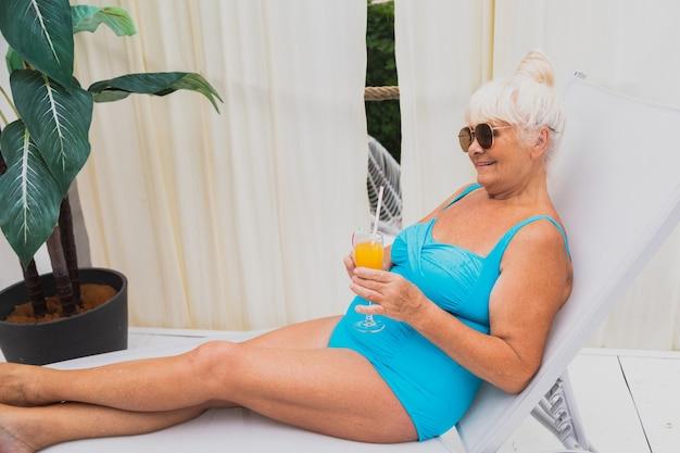 Mulher idosa feliz dando uma festa na piscina - bela senhora idosa tomando banho de sol e relaxando em uma piscina privativa durante o verão