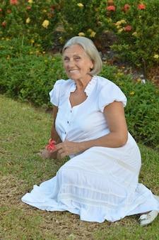 Mulher idosa feliz em jardim tropical ao ar livre
