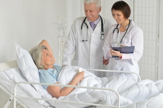 Mulher idosa feliz no hospital com médicos atenciosos