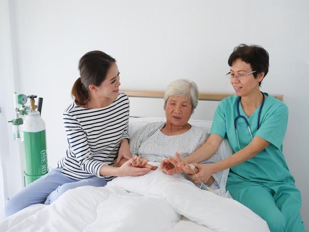 Mulher idosa feliz que fala com enfermeira superior e sua filha na sala de hospital.