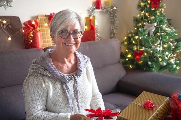 Mulher idosa feliz recebe um novo tablet como presente de natal. um idoso moderno, tecnológico e social, aproveitando as férias de natal