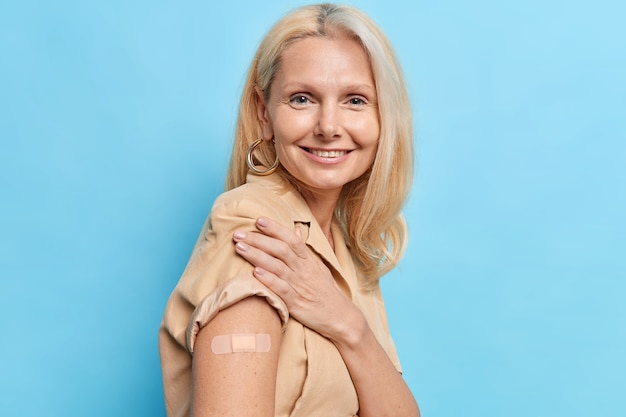 Mulher idosa feliz recebe vacina eficaz contra o coronavírus contra a nova variante delta mostra braço com adesivo no local da inoculação foi vacinado para proteger a saúde e obter passaporte secreto