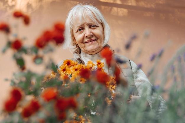 Mulher idosa feliz trabalhando com flores no jardim. aposentada positiva sorrindo