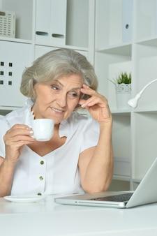 Mulher idosa feliz trabalhando em um laptop no escritório