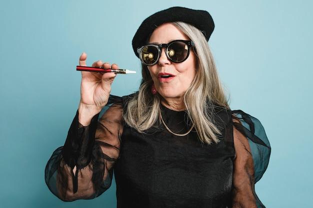 Mulher idosa fumando cigarro eletrônico