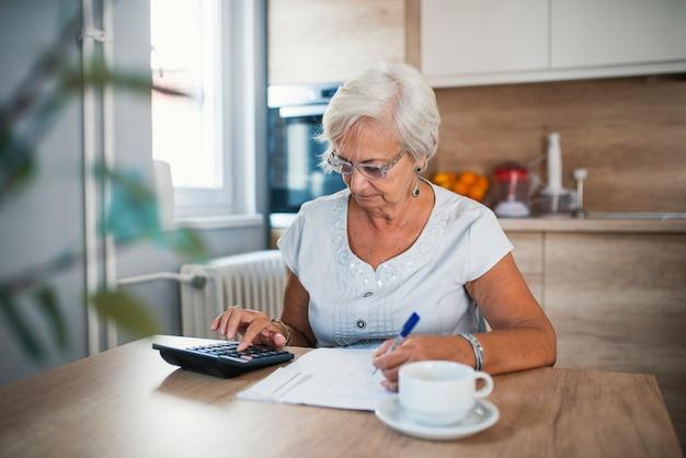 Mulher idosa grave com calculadora sentado à mesa