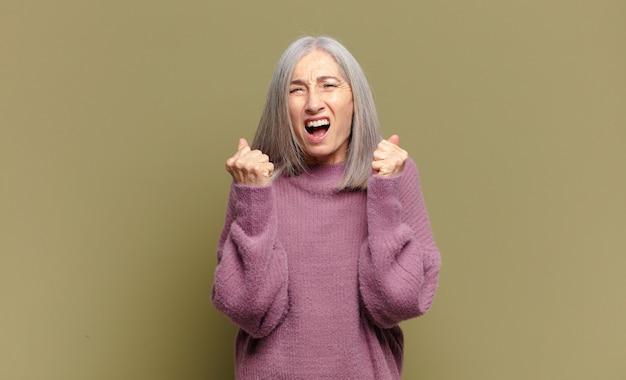 Mulher idosa gritando agressivamente com olhar irritado, frustrado e irritado e punhos cerrados, sentindo-se furiosa
