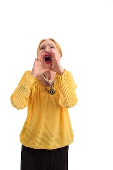 Mulher idosa gritando feminino de mãos dadas perto da boca deixe as pessoas ouvirem você