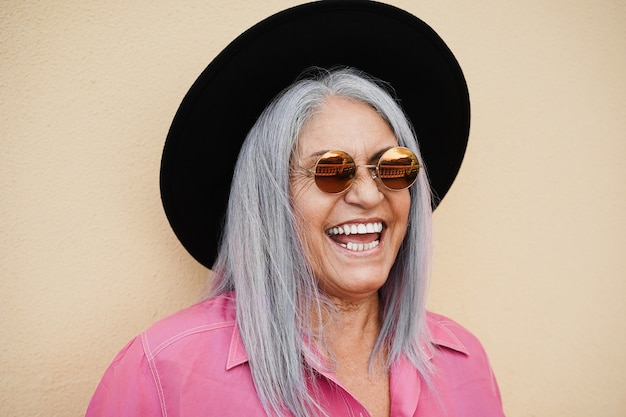 Mulher idosa hippie usando óculos escuros ao ar livre com parede amarela - foco no rosto