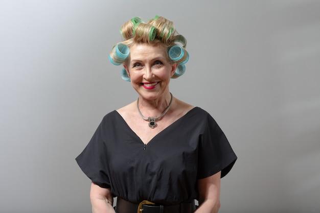 Mulher idosa idosa sorridente dona de casa com rolos de rolos na cabeça do cabelo.