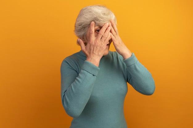 Mulher idosa impressionada usando um suéter azul de gola alta e mantendo as mãos no rosto por entre os dedos