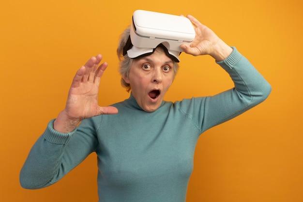 Mulher idosa impressionada vestindo um suéter azul de gola alta e um headset vr levantando um headset vr olhando para a frente e mantendo a mão no ar isolada na parede laranja
