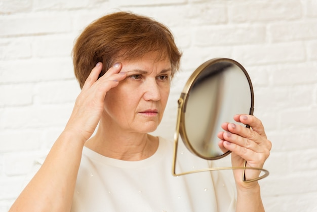 Mulher idosa infeliz olhando no espelho em casa, tocando rosto enrugado, processo de envelhecimento