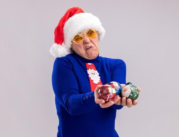 Mulher idosa insatisfeita usando óculos de sol com chapéu de papai noel e gravata de papai noel segurando enfeites de bola de vidro