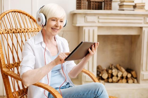 Mulher idosa inteligente e produtiva usando seu tablet para assistir a alguns vídeos legais enquanto está sentada em uma cadeira e usando fones de ouvido