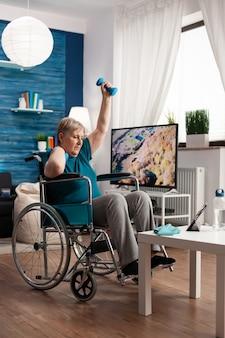 Mulher idosa inválida em cadeira de rodas assistindo exercícios corporais na academia em um tablet na sala de estar exercitando músculos dos braços usando halteres