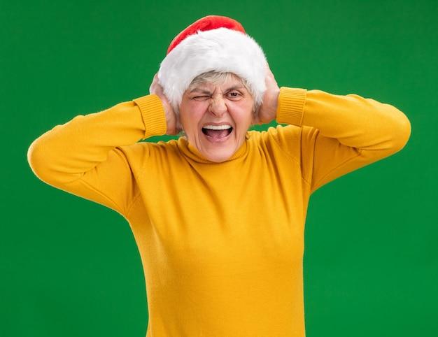 Mulher idosa irritada com chapéu de papai noel cobrindo as orelhas com as mãos isoladas na parede roxa com espaço de cópia