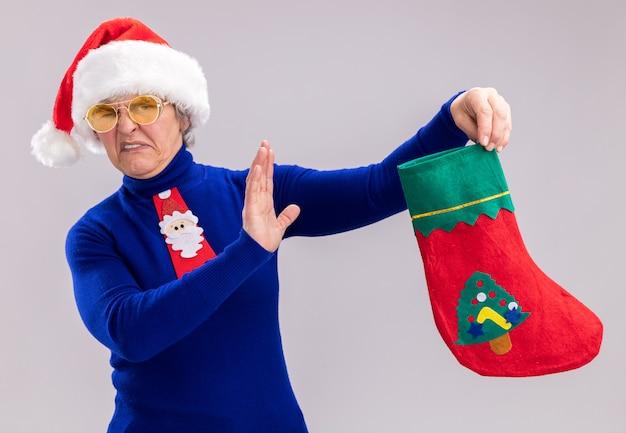 Mulher idosa irritada usando óculos de sol com chapéu de papai noel e gravata de papai noel segurando uma meia de natal isolada na parede branca com espaço de cópia