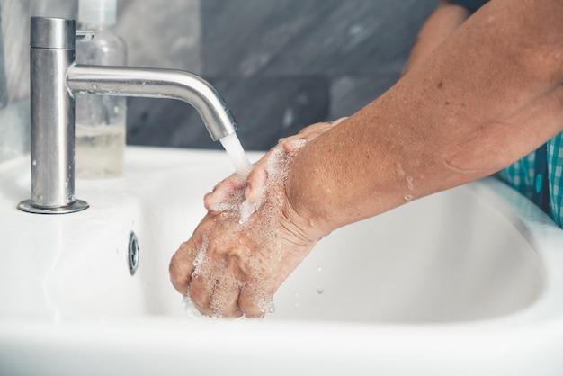 Mulher idosa lava as mãos para prevenção da nova doença do coronavírus 2019 ou covid-19