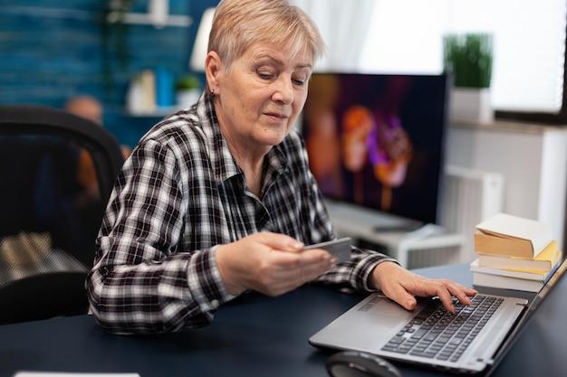 Mulher idosa lendo código cvv do cartão de crédito Foto Premium