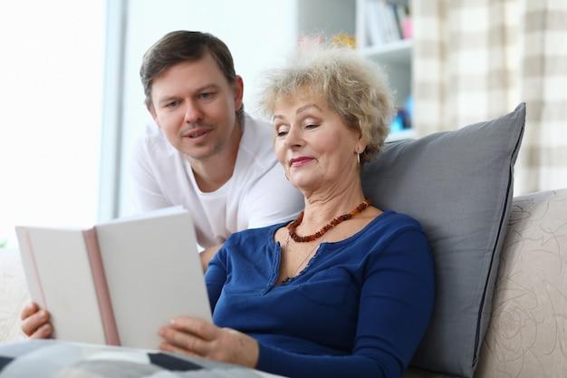 Mulher idosa lendo livro com o filho adulto