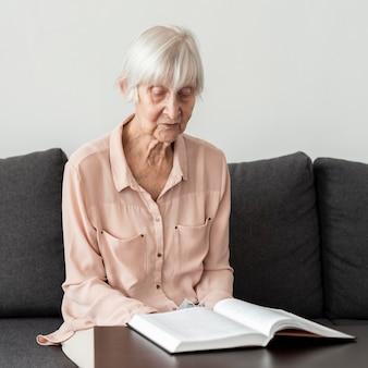 Mulher idosa lendo um livro na casa de repouso