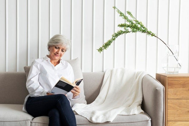 Mulher idosa lendo um livro no sofá em uma sala de estar com decoração escandinava