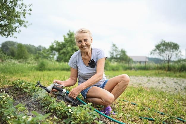 Mulher idosa madura regando plantas com mangueira de água. conceito de agricultura, jardinagem, agricultura, velhice e pessoas