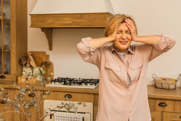 Mulher idosa madura sênior que sofre de depressão na cozinha em casa, estresse doméstico.