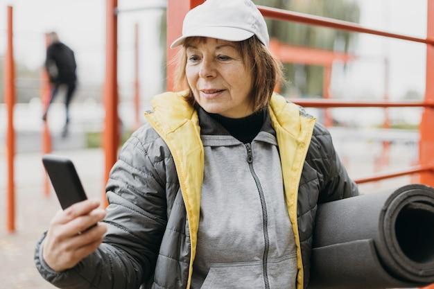Mulher idosa malhando ao ar livre segurando o smartphone e o tapete