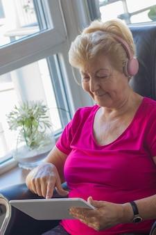 Mulher idosa manipulando dispositivos eletrônicos para distração e informação