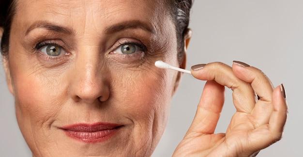 Mulher idosa maquiada usando cotonete para removê-la
