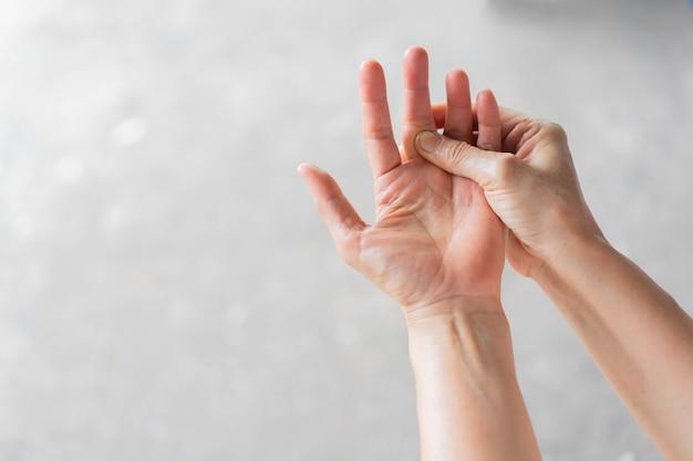 Mulher idosa massagem nos dedos para aliviar a dor