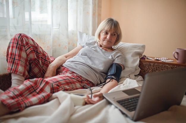 Mulher idosa na cama olhando para a tela do laptop e consultando um médico online em casa, telessaúde