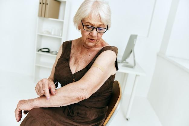 Mulher idosa na clínica, passaporte de vacina covid