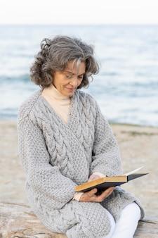Mulher idosa na praia lendo um livro