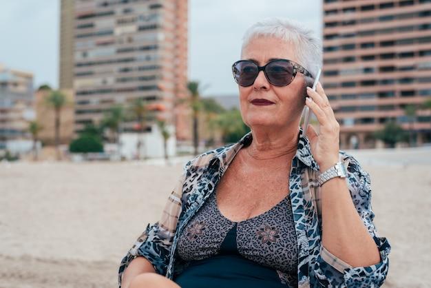 Mulher idosa na praia no telefone celular