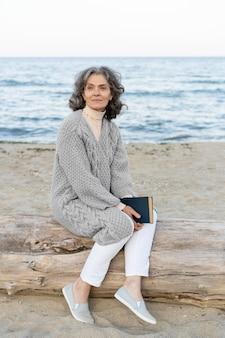 Mulher idosa na praia segurando um livro