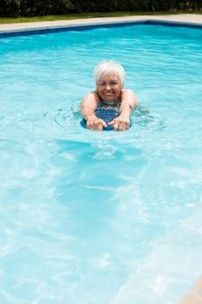 Mulher idosa nadando na piscina em um dia ensolarado