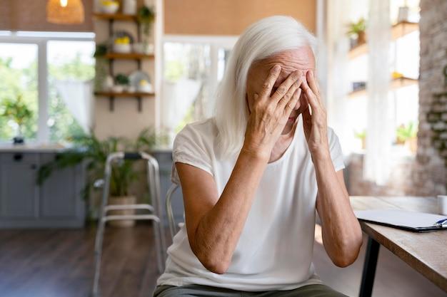 Mulher idosa não se sentindo bem em casa