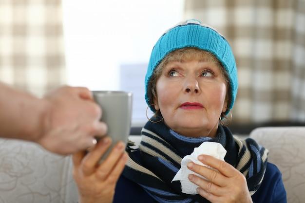Mulher idosa no cachecol e chapéu senta-se no sofá em casa