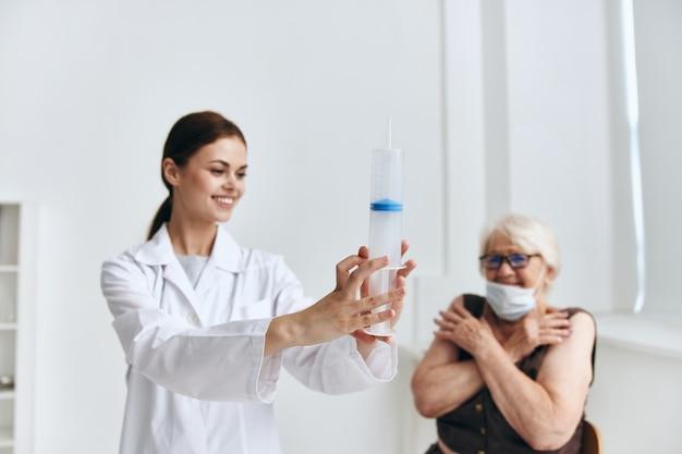 Mulher idosa no divertimento de injeção de mão de nomeação do médico