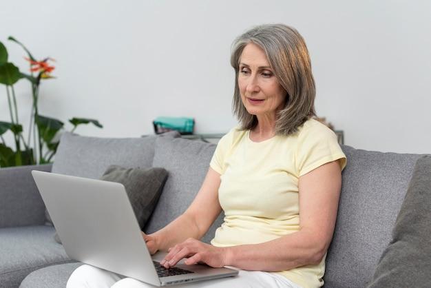Mulher idosa no sofá em casa usando laptop Foto gratuita