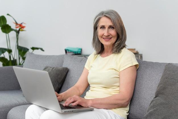 Mulher idosa no sofá em casa usando laptop