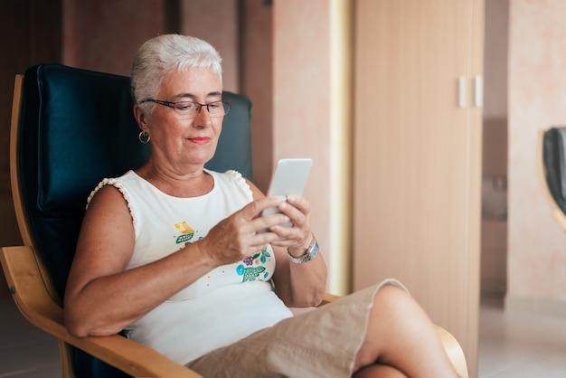 Mulher idosa no telefone celular em casa