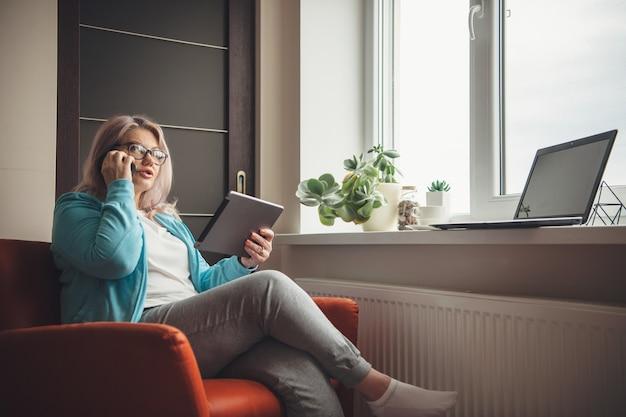 Mulher idosa ocupada com cabelo loiro e óculos, segurando um tablet e falando no telefone, enquanto trabalha em casa