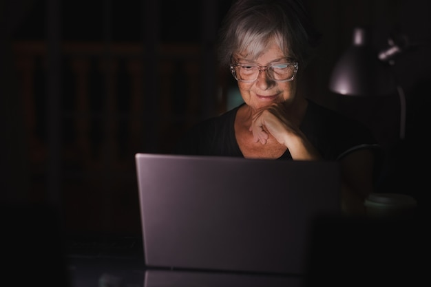 Mulher idosa olhando e usando laptop em casa tarde da noite, trabalhando assistindo vídeos no computador