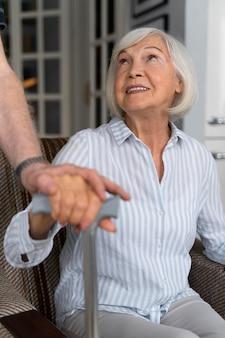 Mulher idosa olhando para seu cuidador
