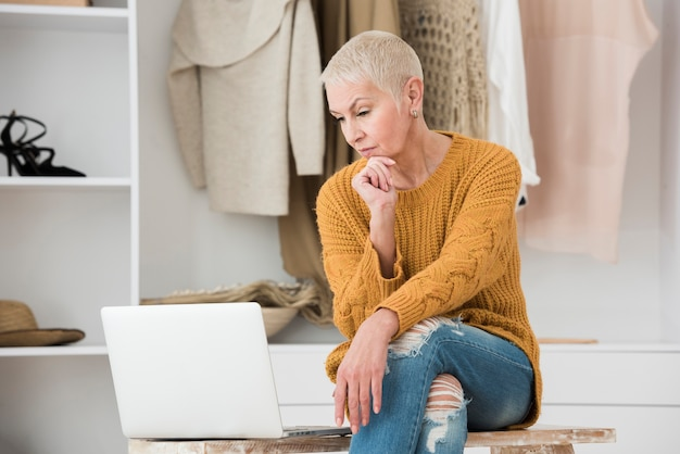 Mulher idosa olhando pensativamente para laptop