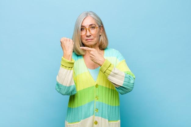 Mulher idosa ou de meia-idade com aparência impaciente e zangada, apontando para o relógio, pedindo pontualidade, querendo ser pontual